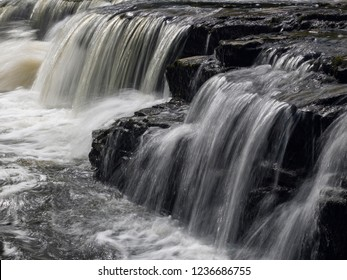 Water flowing over rocks at Aysgarth Falls on the River Ure in Wensleydale in the Yorkshire Dales in the north of England.