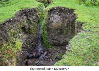 Water flowing through a crevice in the earth wwith lush green grass. Soil ersosion. Landslide.