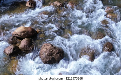 Water flowing through a group of rocks in a river.