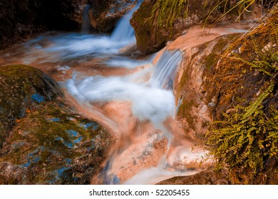 Water flows around stones in a long exposure.