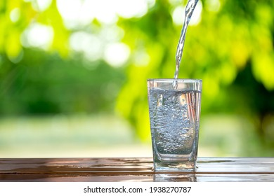 Water flows into a glass placed on a wooden bar. - Shutterstock ID 1938270787