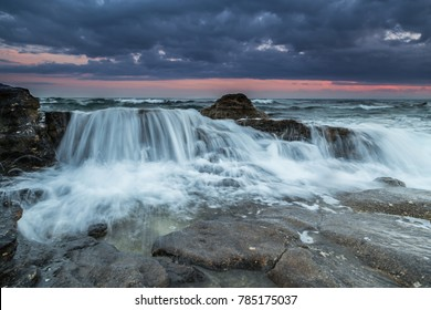 Water flows into the rocky beach