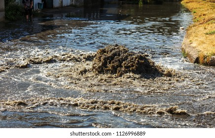 Water flows out of road sewage hatch. Drainage fountain of sewage. Accident of sewage system. Dirty sewage water flows fountain on road. From hatch fountain flows water