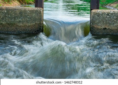 Water flows through the floodgate in the irrigation canal quickly.Water management, irrigation system, irrigation dam, irrigation canal To send to agricultural plots. To solve drought in northeast
