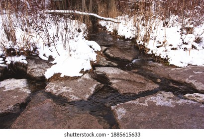 Water flows through rocks on the ground during winter at the Scarborough Bluffs.
