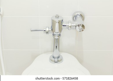 Water flush valve for water closet or flush toilet inside toilet room. Wall decor with ceramic tile material in background. Clean and shiny conditioner appropriate to use.