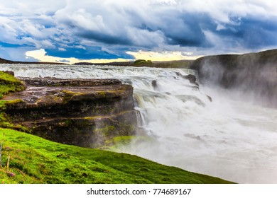 Water fog and foam fly over the waterfall. Cascade waterfall Gullfoss in Iceland. The concept of extreme and phototourism