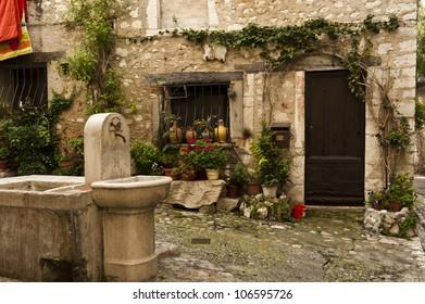 A water fountain near a door entrance to medieval home in Saint-Paul-de-Vence.