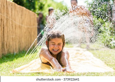 Water fun in garden - girl cooling down with water sprinkler on garden slide