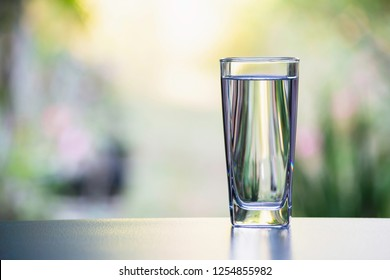 Water in the glass on table with nature background