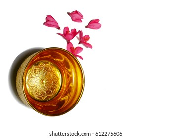 water in a gold cup and pink flower decoration on white background