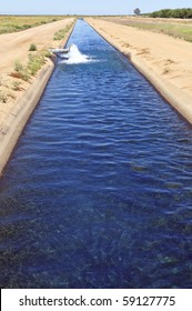 Water gushes from pipe into California irrigation canal