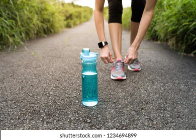 Water and health. female runner tying shoe next to water bottle.