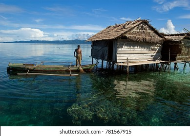 Water house and fisherman in his canoe, Raja Ampat Indonesia, May 2014.