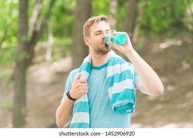 Water is indispensable for human health. Fit athlete having a drink from water bottle during training outdoor. Thirsty sportsman drinking pure water on hot summer day. Keeping body water balance.