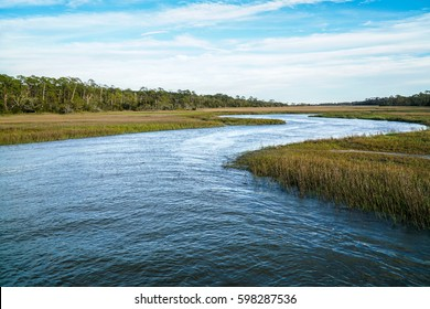 A water inlet from the ocean runs into marsh land and grass or reeds, under a blue sky with thin clouds, a man made project to increase the oyster population in the area are Jekyll Island, Georgia.