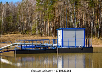 Water intake station at the pond. Metal pantons and fences. Waterpipes with insulation. Room with an electric pump. Concept of water supply from reservoirs.