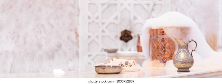 Water jar, towel and copper bowl with soap foam in turkish hamam. Traditional interior details. Horizontal, wide screen format, banner format