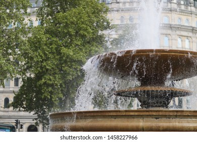 Water jets, flying up over the bowl of a large fountain on the city street
