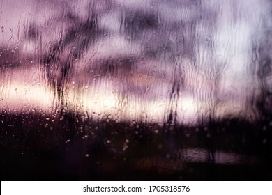 water jets over glass, rain outside view through a window, blurred view of a street through a wet window. Purple tone. Rain in the evening during sunset. Picturesque autumn sunset blurred
