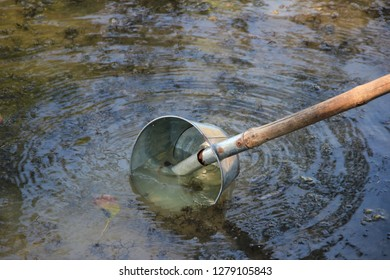 Water ladle made from aluminum sheet The handle is made from dried bamboo trees as a hand-made work to be used to scoop water in the garden beside the ditch. Water in the ditch is very clear.