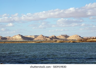 Water lake with rock mountains background in sand desert oasis in blue sky cloudy daylight  in siwa oasis tourism spot in Egypt