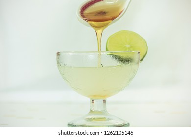 water lamon and hony bee in cristal glass with white background