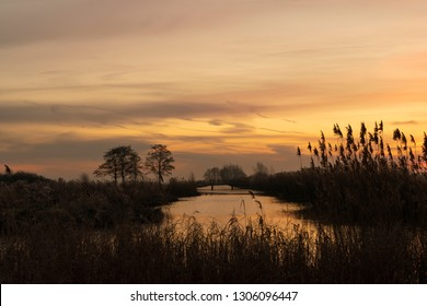 Water landscape at sunrise with reeds in the foreground, a ditch, bridge and orange colored sky. Silhouettes of bare trees.