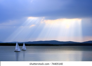 Water landscape with two yachts and sunshine in the background