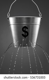 Water leaking from bucket with the concept of finance and losing money