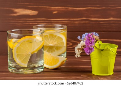 water with a lemon on a wooden background