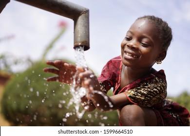 El agua es vida para los niños africanos, la niña grandiosa negra que bebe de la basura