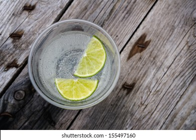 water with lime in a plastic cup on wooden table