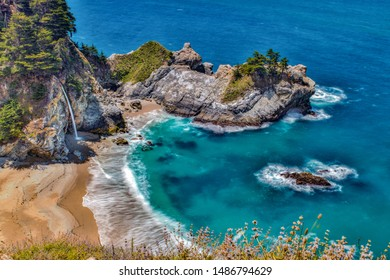 Water from McWay Falls descends on beach at the McWay Cove in Big Sur, California.