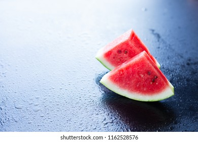 Water melon slices on a black background, selective focus