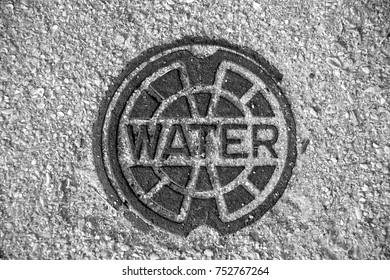 water meter lid metal looking down background black and white photograph