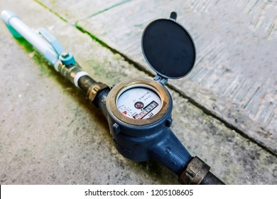 Water meter on concrete background, Measuring device, Open cover of water meter to check counter number of water consumption, water pipe and meter with waterspout of home