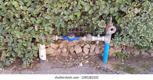 water meter on a pipe near stone wall covered with leaves outside building in the city