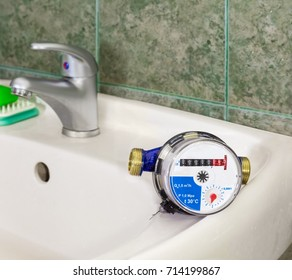 Water meter on the wash basin on background of a handle mixer tap and wall with green tiles