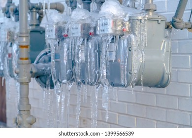 Water meters and gray pipes covered with against a white brick wall