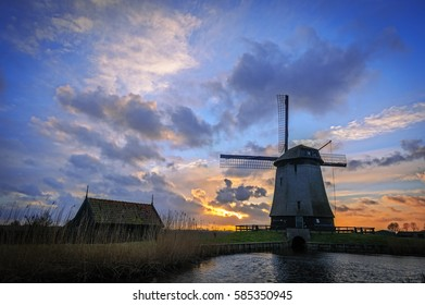 Water mill beside an Eilandspolder canal in sunset, the Netherlands