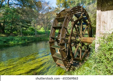 Water mill wheel on river on sunny day. Sustainable energy and water power traditional machinery