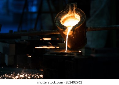 Water molten metal Being poured from the crucible Into the sand mold