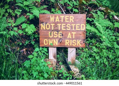 """""""Water not tested use at own risk"""" sign in the woods"""