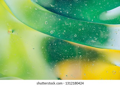 Water oil bubble macro abstract background flow liquid green yellow colors