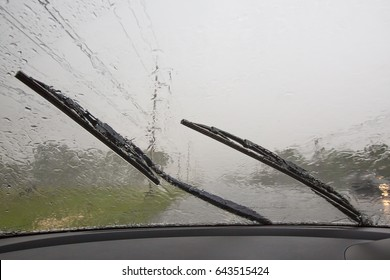 Water on glass and windshield from inside a car while raining. Wipers are working while rains heavily. the car was running slowly through the rain, with caution on the road with the car running around