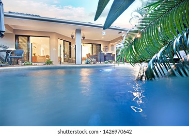 Water on swimming pool with sunlight, natural trees and green grass are beautiful, sunlight around the area, weather is good, outside of a home garden.