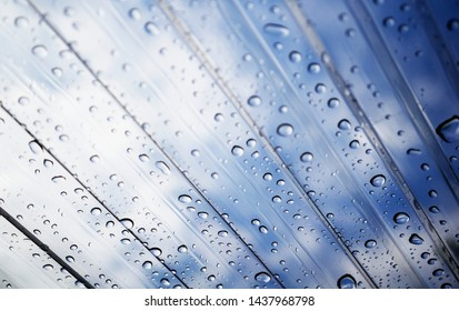 Water on a transparent roof. View of the sky through the transparent roof and raindrops.