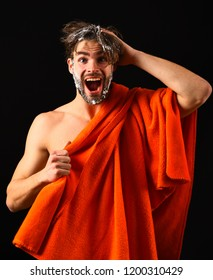 Water is over. Macho attractive nude guy black background. Man bearded tousled hair covered with foam or soap suds. Wash off foam with water carefully. Man with orange towel ready to take shower.