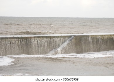 water over sea wall and running down steps